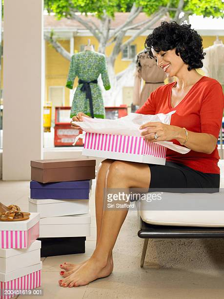 Female customer opening shoe box in shop