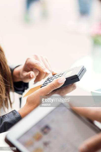 Female customer paying through card reader while owner using digital tablet in food truck