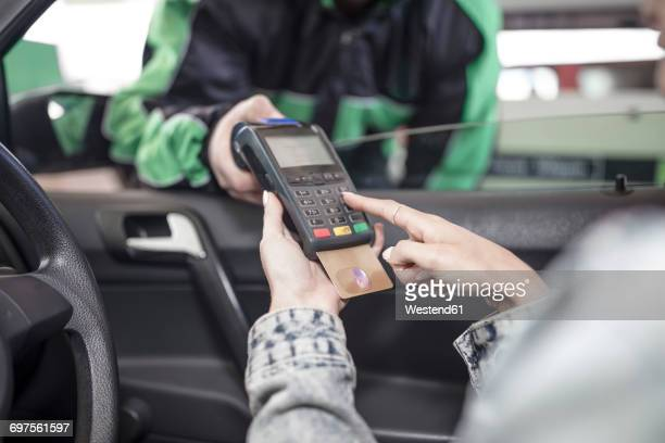 Female customer paying with credit card at the fuel station