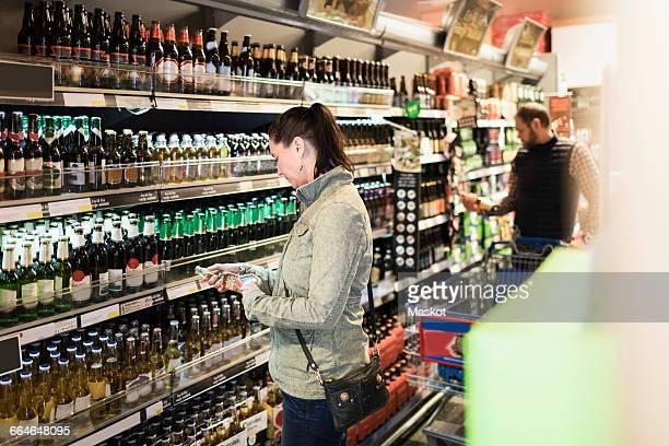 Female customer scanning beer bottle in supermarket