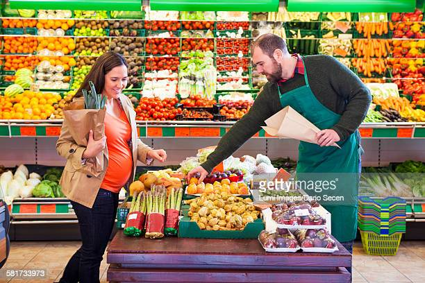 Female customer shopping in greengrocers shop
