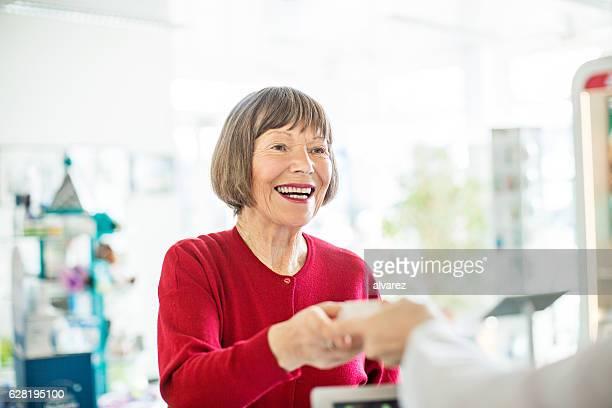 Female customer taking medicine from pharmacist