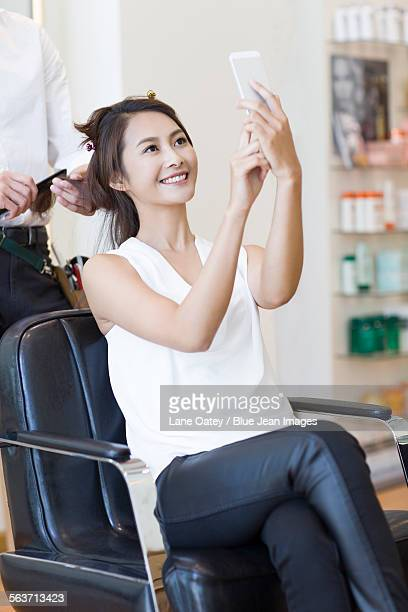 Female customer taking self portrait in barber shop