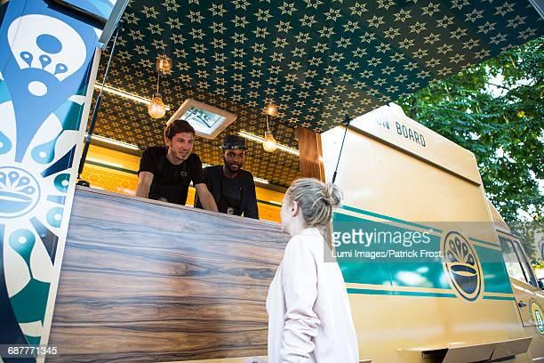 Female customer talking to vendors at food truck