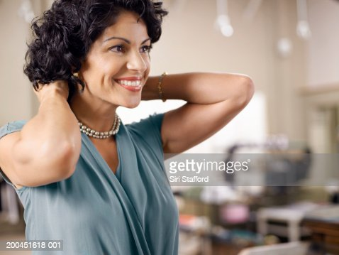 Female customer trying on pearl necklace in shop