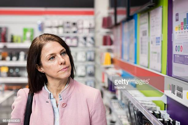 Female customer viewing technology in electronics store