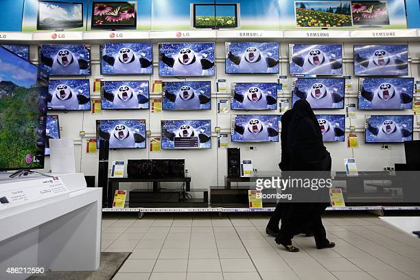 Female customers browse Samsung Electronics Co and LG Electronics Inc flat screen televisions displayed in an electronics store at the Hyperstar...