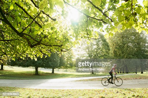 Female cycling through parkland