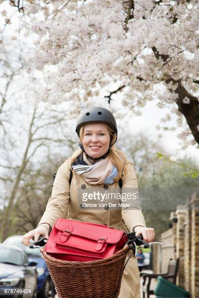 Female cyclist cycles in urban street at spring time.