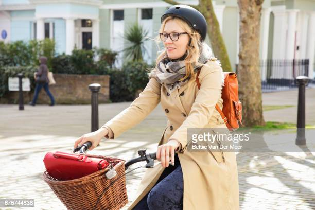 Female cyclist cycles in urban street on her way to work.