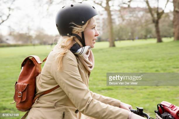 Female cyclist cycles through public park in city.