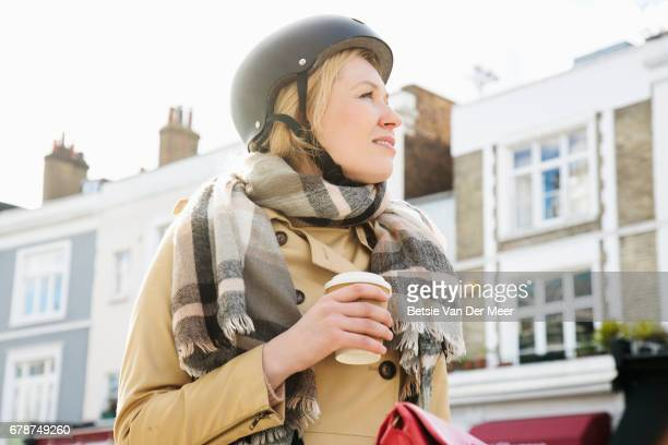 Female cyclist is drinking take away coffee in urban street.