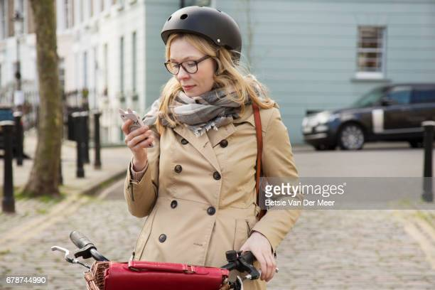 Female cyclist looks at messages on phone, while leaning back on bike in urban street.