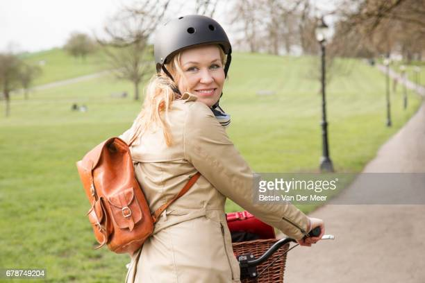 Female cyclist looks over shoulder in public park.