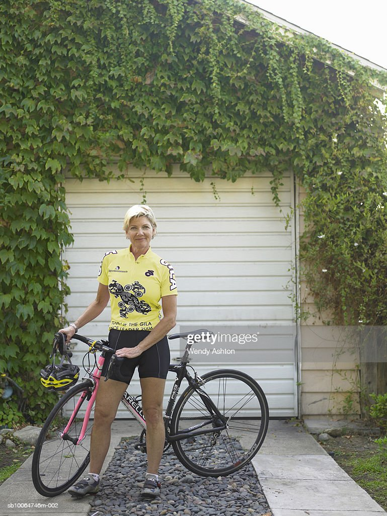 Female cyclist with bicycle in driveway, smiling, portrait : Stock Photo
