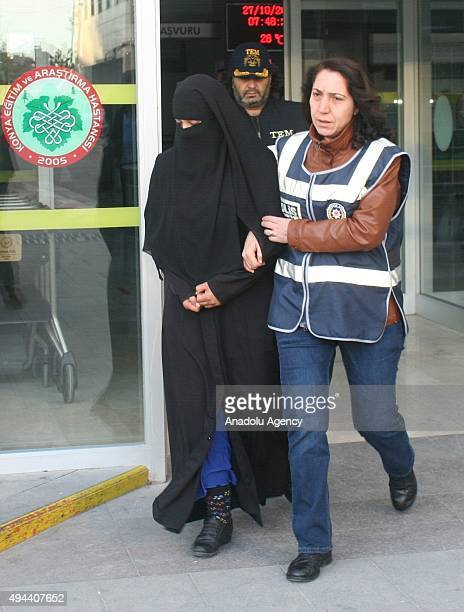 A female Daesh suspect among 30 others is seen as being escorted under arrest by a police officer to health check after an antiterror operation...
