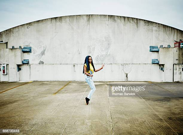 Female dancer balancing on tiptoes on rooftop
