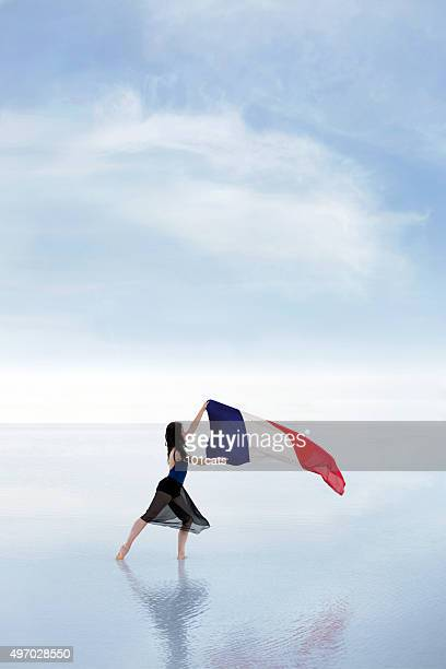 Female dancer carrying French flag waving in the wind outdoors