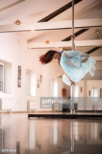 Female dancer in motion on a dancing pole.
