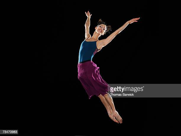 Female dancer leaping in air, smiling, arms extended
