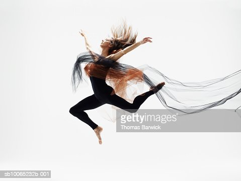 Female dancer leaping in mid air against white background, side view : Stock Photo
