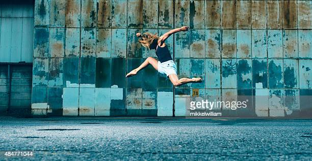 Female dancer runs and jumps into the air