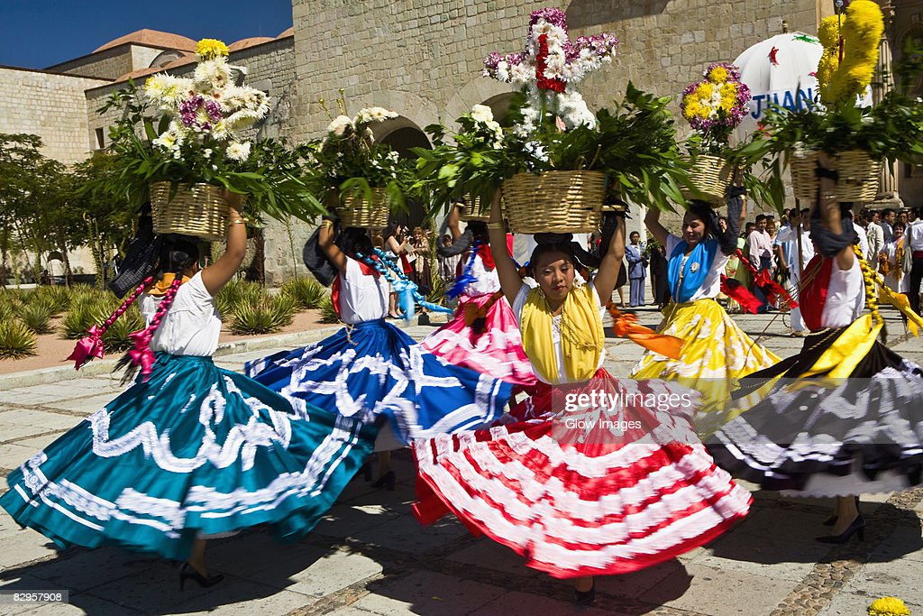Female dancers dancing with potted plant over their head, Oaxaca, Oxaca State, Mexico