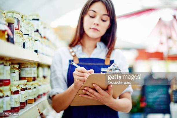 Female deli owner writing on clipboard by shelves in shop
