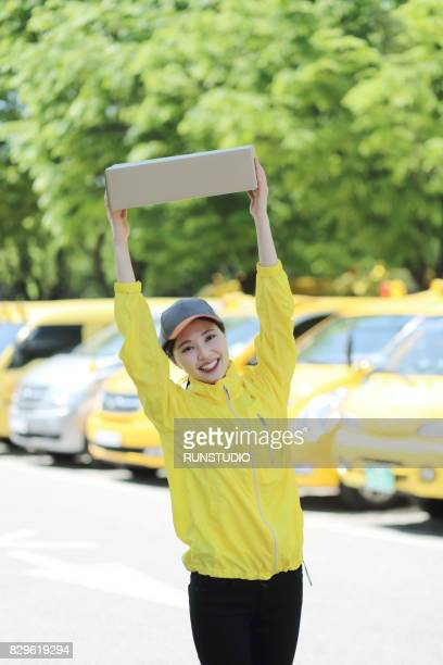 Female delivery person smiling and holding box