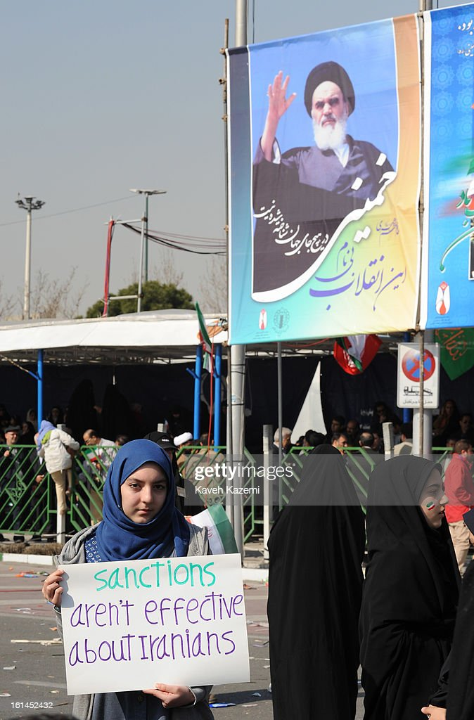 A female demonstrator holds a banner defying international sanctions as a result of Iran's nuclear program during the 34th anniversary of the Islamic revolution in Azadi square on February 10, 2013 in Tehran, Iran.