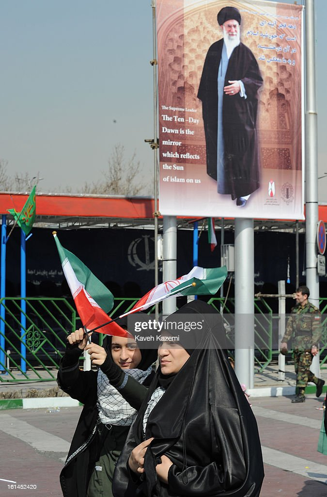 Female demonstrators in black chador walk past a large banner of Ayatollah Ali Khamenei carrying small Iranian flags during the 34th anniversary of the Islamic revolution in Azadi square on February 10, 2013 in Tehran, Iran.