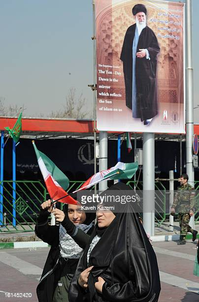 Female demonstrators in black chador walk past a large banner of Ayatollah Ali Khamenei carrying small Iranian flags during the 34th anniversary of...
