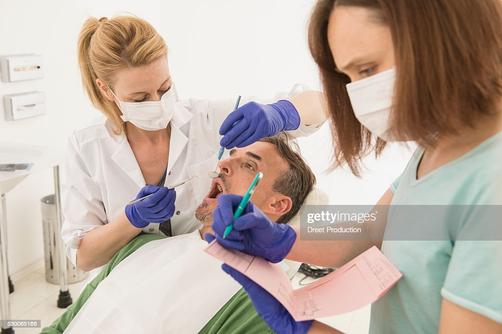 Female dentist examining patient and dictating the findings to the assistant, Munich, Bavaria, Germany