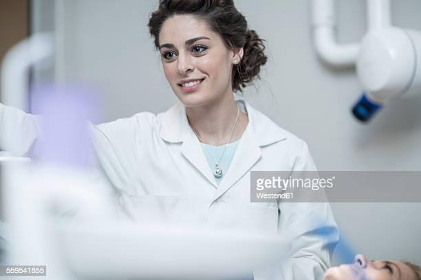 Female dentist preparing for treatment of patient