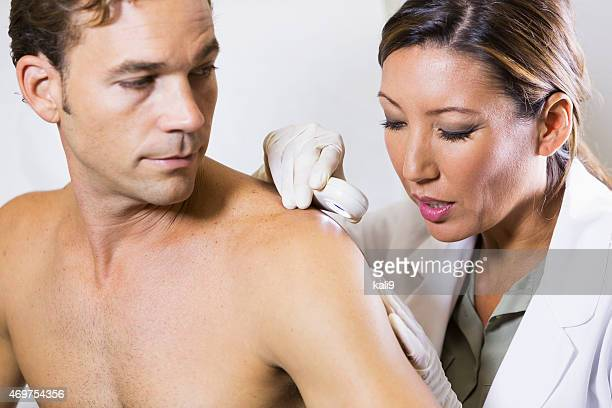 Female dermatologist examining a male patient
