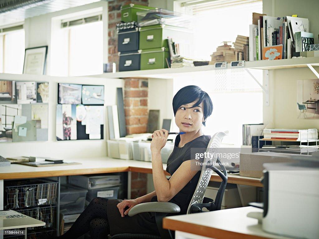 Female designer at desk in office head turned : Stock Photo