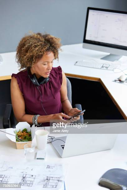 Female designer looking at smartphone during working lunch at office desk