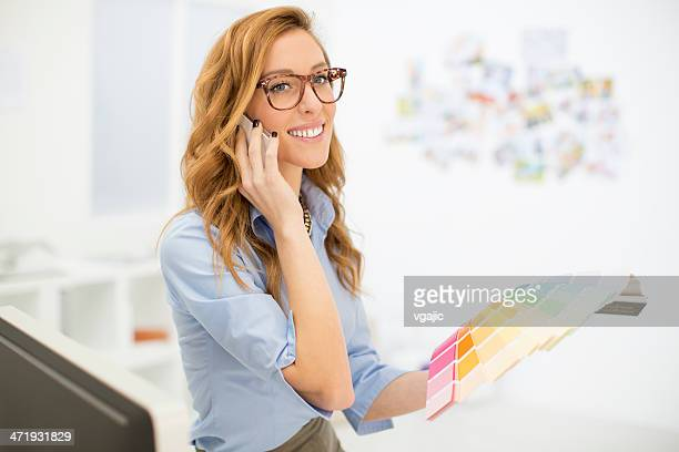 Female Designer Talking On The Phone At Work.