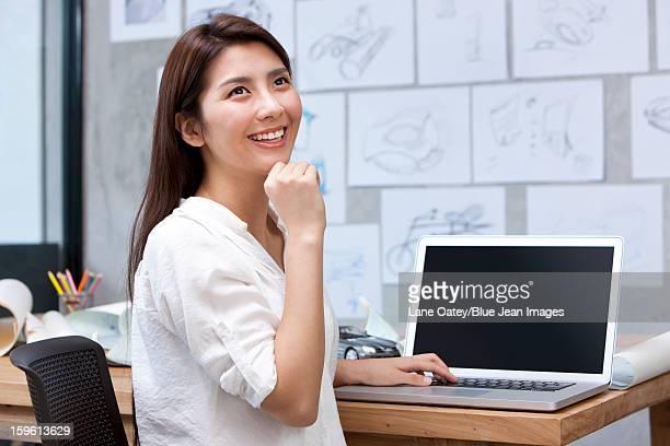 Female designer using laptop in studio