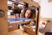 Female Designer Working With 3D Printer In Design Studio