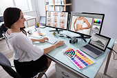 Happy Young Female Designer Working With Photographs On Multiple Computer At Workplace