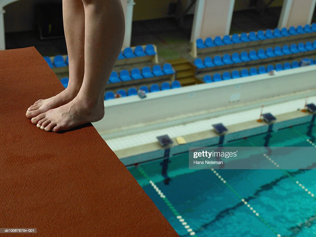 Female diver standing on edge of diving board, low section : Stock Photo