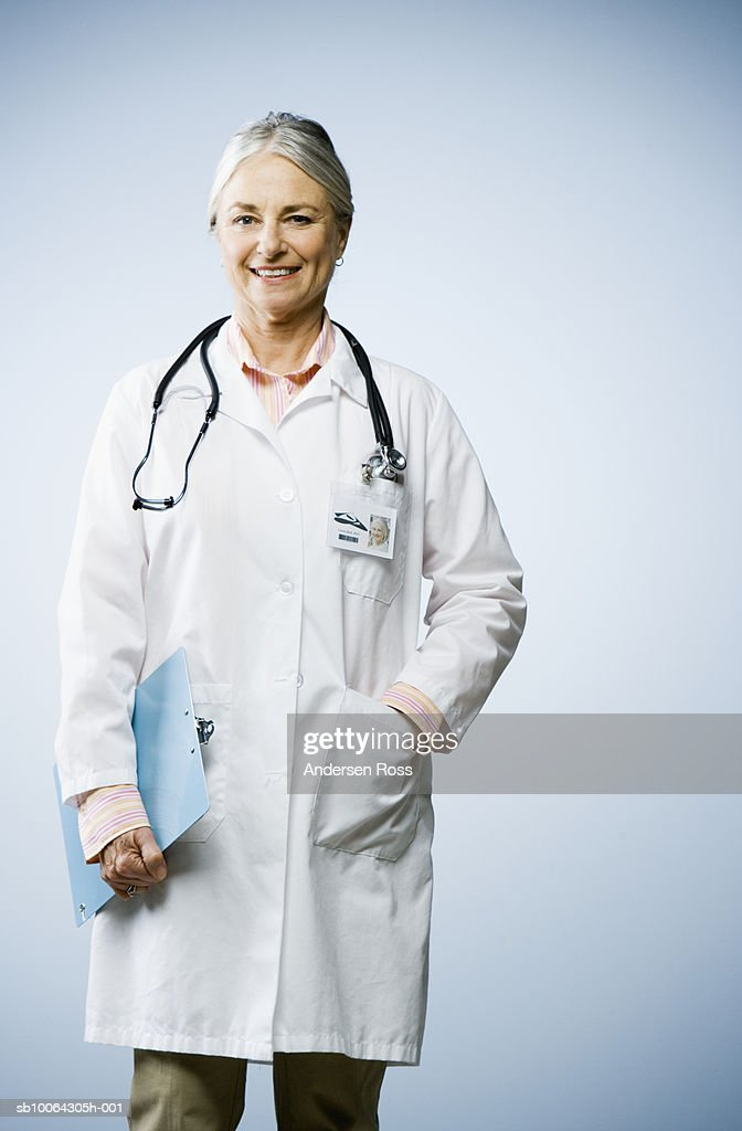 Female doctor, against white background, portrait : Stock Photo
