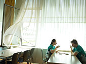 Female doctor and male doctor in cafeteria by window