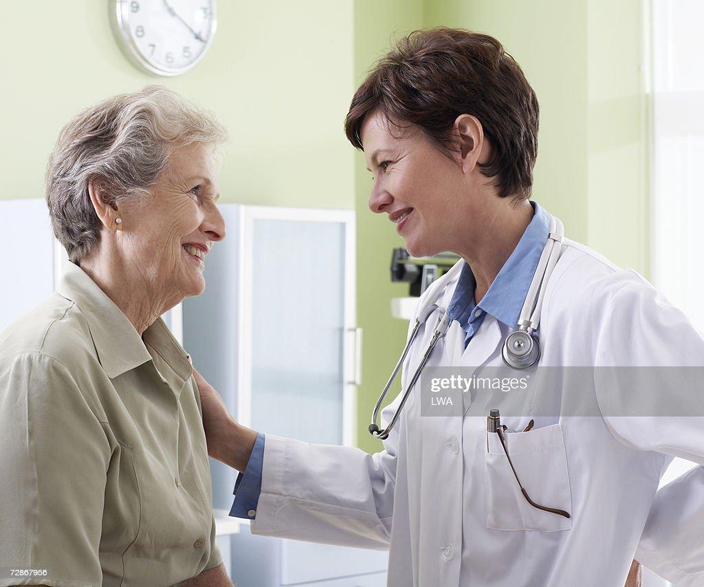 Female doctor assisting senior woman, smiling : Stock Photo