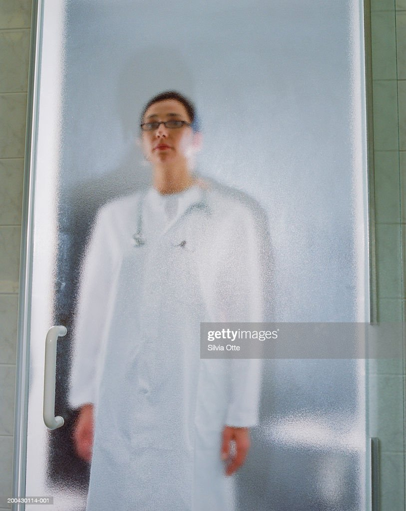 Female doctor behind glass door, portrait : Stock Photo