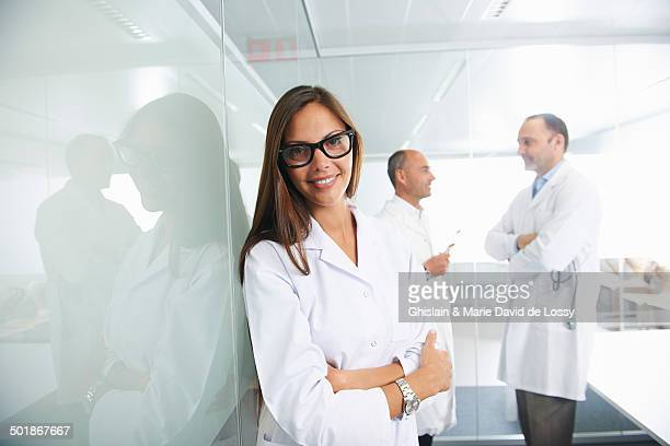 Female doctor by reflective wall, colleagues in background