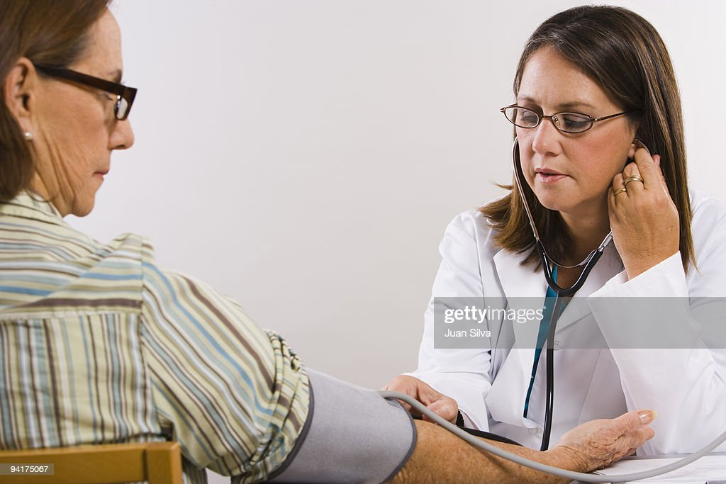 Female doctor checking blood pressure of patient : Stock Photo