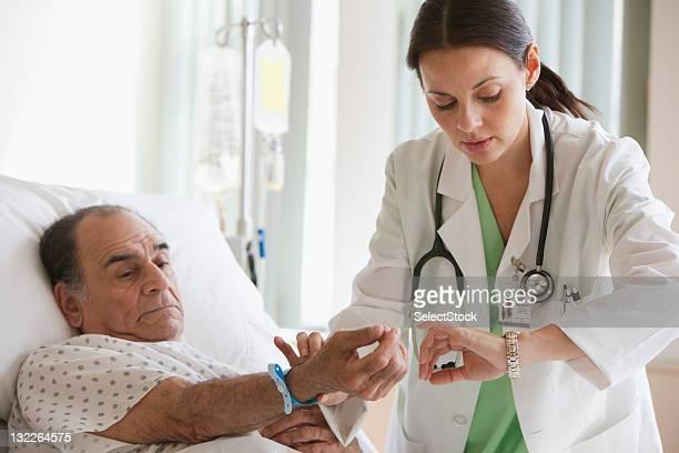 Feminino médico verificar a taxa de pulso do doente