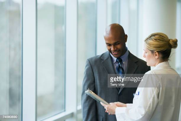Female doctor discussing chart with businessman